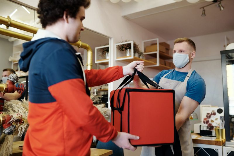man in a face mask handing over a thermal bag to another man