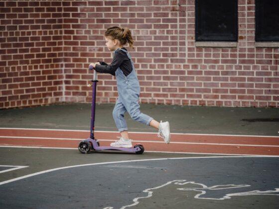 little girl riding scooter on stadium