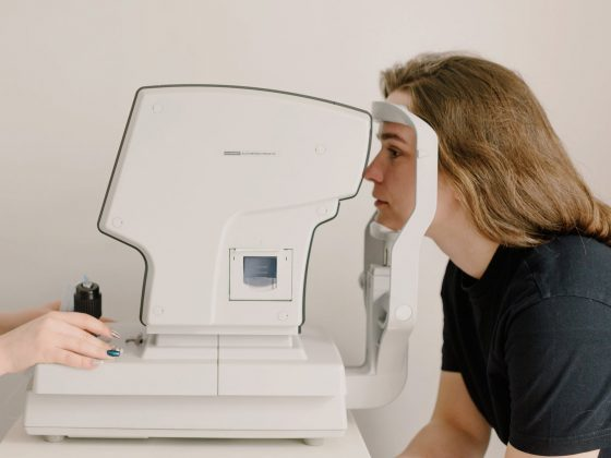 unrecognizable ophthalmologist scanning eyes of woman on vision screener