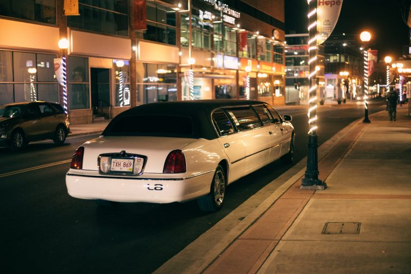 modern limousine on road with shiny lights in night town
