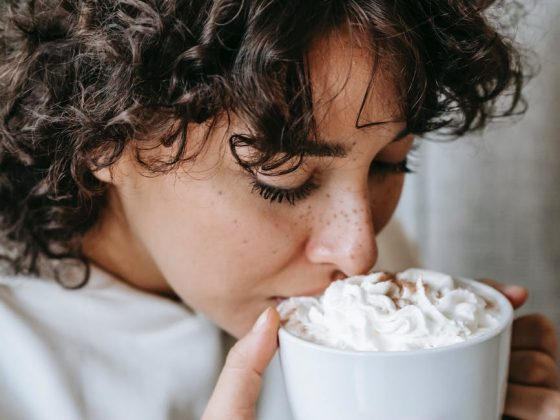 charming female drinking hot coffee with whipped cream